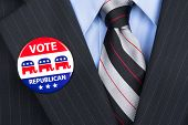 A republican voter proudly wears his party pin on his suit lapel.