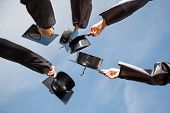 stock photo of faceless  - Directly below shot of students raising mortar boards against sky on graduation day - JPG