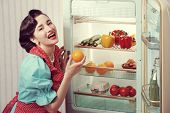 image of refrigerator  - Cheerful woman posing with an open refrigerator - JPG