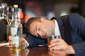 stock photo of over counter  - Unconscious businessman holding whiskey glass lying on a counter in a classy bar - JPG