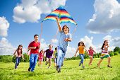stock photo of foreground  - Happy large group of kids boys and girls with kite and laughing boy running on the foreground - JPG