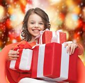 holidays, presents, christmas, x-mas concept - happy child girl with gift boxes