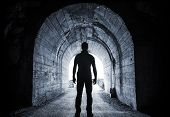stock photo of tunnel  - Young man stands in dark tunnel and looks in the glowing end - JPG