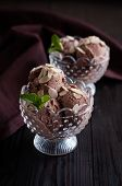 stock photo of frozen food  - Two portions of delicious chocolate ice cream with almonds and mint leaf in crystal bowls and dark brown cloth on a wooden board appetizing dessert food closeup - JPG