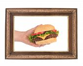 Hand holds hamburger in frame.