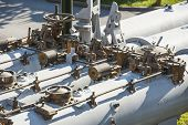 stock photo of top-gun  - Valves and piping on top of an old large naval triple gun - JPG