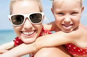 stock photo of children beach  - Young happy mother with little girl on her back - JPG