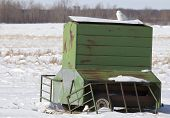pic of snowy owl  - Snowy owl perching on portable farm grain feeder - JPG