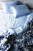 picture of untidiness  - Unmade messy bed with wrinkled sheets from above - JPG