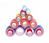 pic of cylinder pyramid  - Colorful hair rollers stacked in pyramid isolated on white background - JPG