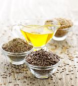 stock photo of flax seed oil  - Bowls of whole and ground flax seed with linseed oil - JPG