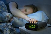 stock photo of frown  - Young woman pressing snooze button on early morning digital alarm clock radio - JPG