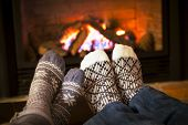 stock photo of hot couple  - Feet in wool socks warming by cozy fire - JPG