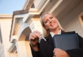foto of real-estate agent  - Female Real Estate Agent Handing Over Keys in Front of Beautiful House - JPG