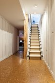 image of upstairs  - Stairway to finished basement in home interior with wood paneling and cork flooring - JPG