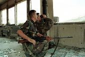 MOSTAR, BOSNIA - AUGUST 16: A Bosnian-Croat HVO sniper team peers out of a destroyed bank building a