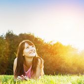 pic of harmony  - Young beautiful woman smiling and lying on the grass at summer sunset looking at the sky - JPG