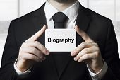 stock photo of plagiarism  - businessman in black suit holding sign biography - JPG