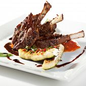 foto of lamb chops  - Roasted Lamb Chops on Tomato Sauce Garnished with Vegetables and Basil - JPG