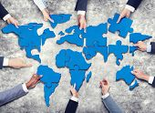 picture of jigsaw  - Group of Business People with Jigsaw Puzzle Forming in World Map - JPG