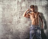 stock photo of break-dance  - Athletic trendy handsome shirtless young man in a hat doing a break dance routine - JPG