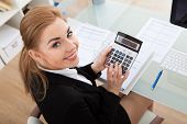 stock photo of financial audit  - Portrait Of Happy Young Businesswoman Sitting At Desk Calculating Finance