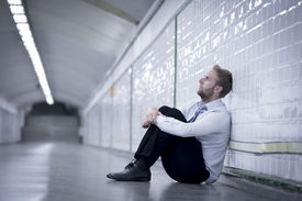 stock photo of underworld  - Young business man who lost job abandoned lost in depression sitting on ground street subway suffering emotional pain thinking and leaning on wall alone