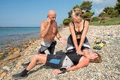 stock photo of prone  - Scuba Divers performing CPR training on a casualty on a beach - JPG