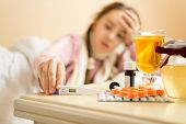 picture of sick  - Out of focus portrait of sick girl lying in bed and taking thermometer from table - JPG