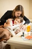 stock photo of sick  - Portrait of young caring mother kissing in head sick daughter in bed - JPG