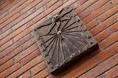 stock photo of sundial  - Sundial on a brick wall in town - JPG