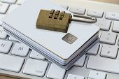 image of combinations  - Batch of Credit or debit Cards with a combination lock on a modern silver keyboard - JPG