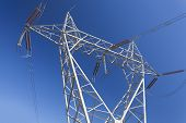 foto of electricity pylon  - Electricity pylon with high voltage power lines against blue sky - JPG