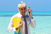 stock photo of flipper  - A well dressed businessman on a tropical island - JPG