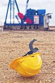 picture of oil derrick  - Protective Helmet and Pumpjack Oil Pump operating on natural gas in the field pumping from the oil well - JPG