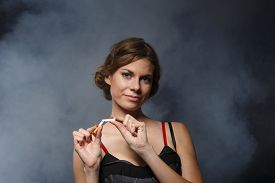 pic of tobacco smoke  - Happy young confident woman quitting smoking stands with the broken cigarette on a dark background with smoke - JPG
