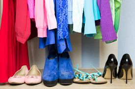 picture of apparel  - Dressing closet with color coordinated clothes on hangers and shelf - JPG