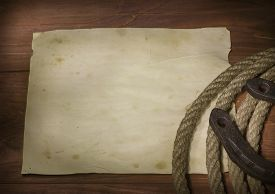 picture of horseshoe  - Old paper background with cowboy lasso and horseshoe on wood texture - JPG