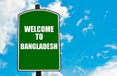 stock photo of bangladesh  - Green road sign with greeting message WELCOME TO BANGLADESH isolated over clear blue sky background with available copy space - JPG