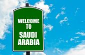 image of saudi arabia  - Green road sign with greeting message WELCOME TO SAUDI ARABIA isolated over clear blue sky background with available copy space - JPG
