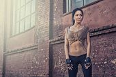 stock photo of rap-girl  - beautiful young athletic girl sitting near the old wall - JPG