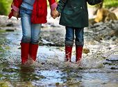 stock photo of boot  - Children wearing rain boots jumping into a mountain river - JPG