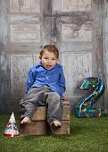 picture of birthday hat  - Adorable toddler sitting on a crate with a birthday party hat on the ground and a number 2 in the background - JPG