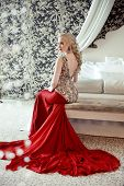 image of evening gown  - Elegant blond woman model wearing in luxurious red gown with long train of dress sitting at modern interior apartment - JPG