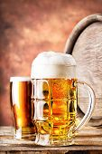 foto of keg  - Mug and a glass of beer with keg on red background - JPG
