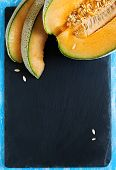 stock photo of cantaloupe  - Cantaloupe Melon Slices on black board with copy space - JPG