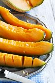 picture of cantaloupe  - Cantaloupe Melon Slices On Metal Rustic Plate - JPG