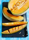stock photo of cantaloupe  - Cantaloupe Melon Slices on black cooking board - JPG