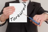 stock photo of torture  - Tortured man in suit cutting text on paper with scissors - JPG