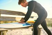 picture of friction  - Active Male Surfer in Wetsuit Preparing his Surfboard by Waxing the Surface of it on Top of the Wooden Bench at the Beach - JPG
